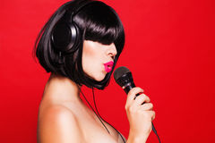 Kobieta słucha muzyka na hełmofonach cieszy się a Zdjęcia Royalty Free