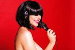 Kobieta słucha muzyka na hełmofonach cieszy się a Zdjęcia Stock