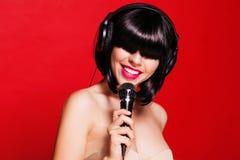 Kobieta słucha muzyka na hełmofonach cieszy się a Zdjęcie Stock