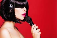 Kobieta słucha muzyka na hełmofonach z Zdjęcia Stock