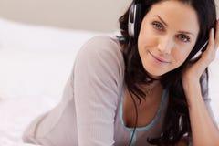 Kobieta słucha muzyka na jej łóżku Zdjęcia Stock