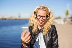 Kobieta słucha muzyka na jej smartphone zdjęcie royalty free