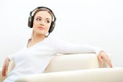 Kobieta słucha muzyka na kanapie obrazy stock