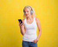 Kobieta słucha muzyka na słuchawki od jej telefonu zdjęcia royalty free