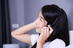 Kobieta słucha muzyka od smartphone na łóżku wewnątrz w hełmofonach obraz stock