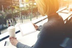 Kobieta słucha muzyka przez cyfrowego stołu, podczas gdy siedzi z bierze oddaloną kawę w kawiarni Fotografia Stock