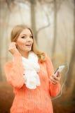 Kobieta słucha muzyka w parku z słuchawkami Obrazy Royalty Free