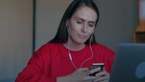 Kobieta słucha muzyka z hełmofonami i tana obsiadanie za miejsce pracy zbiory wideo