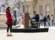 Kobieta słucha uliczny muzyk bawić się pianino Fotografia Royalty Free