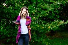 Kobieta słucha muzyka w parku w woolen pulowerze Fotografia Stock