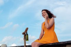 Kobieta sadzająca na molu w tropikalnej lokacji używać jego ono uśmiecha się i smartphone Niebo z chmurami jako t?o zdjęcia stock