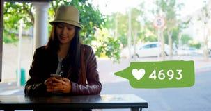 Kobieta sadzająca na stole podczas gdy texting 4k zbiory wideo