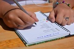 Kobieta sadzająca przy biurkiem, pisze w pociska czasopiśmie fotografia stock