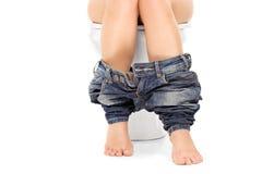 Kobieta sadzająca przy toaletą z ona spodnia zestrzela Zdjęcia Stock