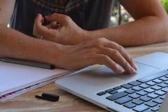 Kobieta sadzająca, używać laptop, ręka na trackpad obraz royalty free