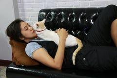 Kobieta sen z białym kotem na czarnej kanapie obrazy royalty free