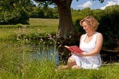 Kobieta siedząca strumienia czytaniem fotografia stock
