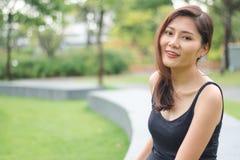 Kobieta siedząca w parku i uśmiechająca się obraz stock