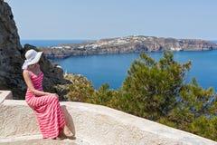 Kobieta siedzi morze i ogląda Grecja Santorini zdjęcie stock