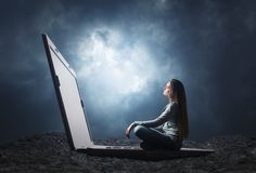 Kobieta siedzi na dużym laptopie Obrazy Royalty Free