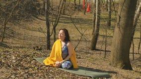 Kobieta siedzi na dywanie z szkocką kratą na ramionach i napój herbacie outdoors zdjęcie wideo