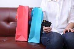 Kobieta siedzi na kanapie z torba na zakupy i trzymać kredytową kartę Obrazy Royalty Free