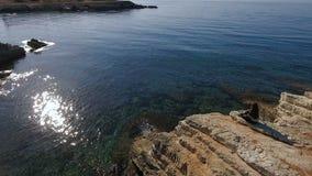 Kobieta siedzi na stonea na enjpys i urwisku piękny widok na morzu zbiory