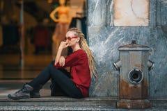 Kobieta siedzi na ulicie blisko kobiety ` s sklepu odzieżowego z blondynek dreadlocks Obrazy Stock