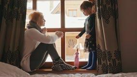 Kobieta siedzi na windowsill i opowiada jej córka zbiory