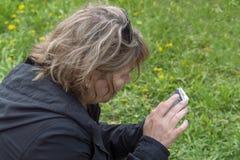 Kobieta siedzi na zielonej trawie i spojrzeniach w smartphone, tylni i bocznego widok, zdjęcie royalty free