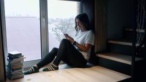 Kobieta siedzi okno i wyszukuje ogólnospołecznych środki w telefonie komórkowym Boczny widok zbiory wideo