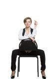 Kobieta siedzi okrakiem na krzesło seksowny przedstawienie nadgarstek obraz stock