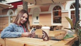 Kobieta siedzi plenerowego pije kawowego ono uśmiecha się i trzyma smartphone w ręce zbiory