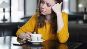 Kobieta siedzi samotnie w kawiarni, sprawdza wiadomość na telefonie póżno dla daty, chłopak zbiory