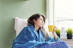 Kobieta siedzi w domu, myśleć z herbatą w ręce fotografia royalty free