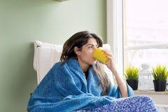 Kobieta siedzi w domu, pijący herbaty obrazy royalty free