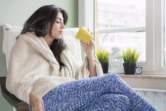 Kobieta siedzi w domu, zawijający w powszechnym, pijący herbaty obraz royalty free