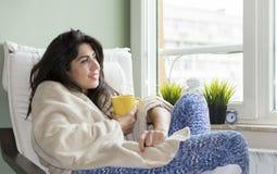 Kobieta siedzi w domu, zawijający w powszechnym, pijący herbaty obraz stock