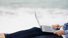 Kobieta siedzi w niebieskich dżinsach i przypadkowej koszula w zamkniętym widoku z technologia cyfrowa laptopu przyrządem zdjęcie wideo