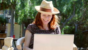 Kobieta siedzi w ogródzie cieszy się rozmowę na jej laptopie w słońcu zbiory wideo