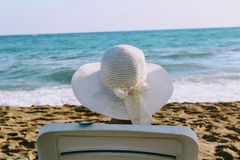 Kobieta siedzi w pokładu krześle przeciw tłu denna kipiel w białym kapeluszu z szerokim rondem Zdjęcia Royalty Free