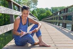 Kobieta siedzi writing na drewnianym moscie Fotografia Royalty Free