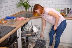 Kobieta składa naczynia w zmywarka do naczyń Kobieta przy kuchnią sprzątanie zdjęcia royalty free