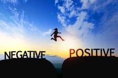 Kobieta skacze przez przerwy między negatywem pozytyw na sunse zdjęcie royalty free