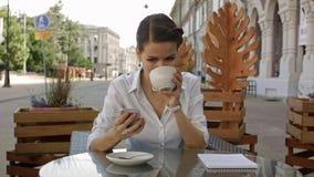 kobieta sms - ów Zbliżenie młoda szczęśliwa ono uśmiecha się rozochocona piękna dziewczyna patrzeje mobilnego telefonu komórkoweg Fotografia Stock