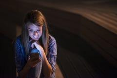 kobieta sms - ów Zbliżenie młoda szczęśliwa ono uśmiecha się rozochocona piękna kobieta patrzeje mobilnego telefonu komórkowego d Zdjęcia Stock