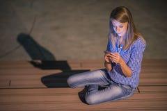 kobieta sms - ów Zbliżenie młoda szczęśliwa ono uśmiecha się rozochocona piękna kobieta patrzeje mobilnego telefonu komórkowego d Obraz Royalty Free