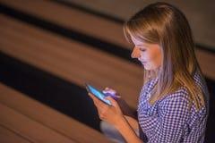 kobieta sms - ów Zbliżenie młoda szczęśliwa ono uśmiecha się rozochocona piękna kobieta patrzeje mobilnego telefonu komórkowego d Fotografia Stock