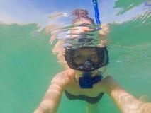 Kobieta snorkeling w tropikalnym nawadnia przed egzotyczną wyspą zdjęcia royalty free