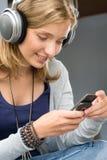 Kobieta sprawdzać szczęśliwych telefon komórkowy jej potomstwa Zdjęcia Stock
